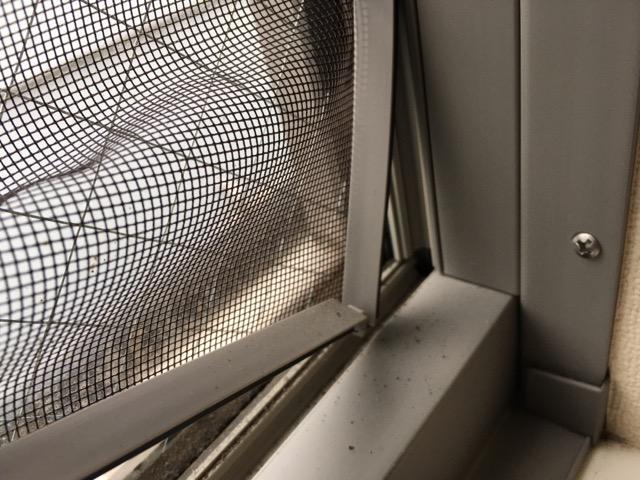 窓の右下から網戸を外した様子